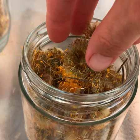 llenar un bote de cristal con flores y hojas secas de árnica